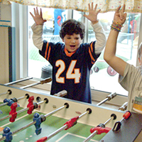 Young child raising hands playing foosball with classmates.