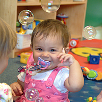 Young infant smiling and playing with bubbles in a classroom.