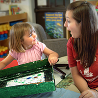 Teacher with young child looking amused and holding an art project.