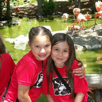 Two children sitting outside by a pond smiling with arms around each other.