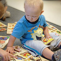 Toddler playing with learning materials at a learning center.